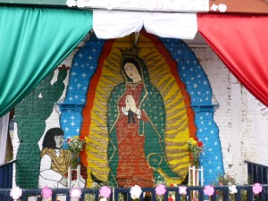 A neighborhood shrine depicts Juan Diego presenting roses to the Virgin