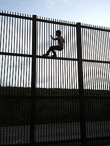 Child scaling the U.S. -Mexico border wall at Brownsville, TX