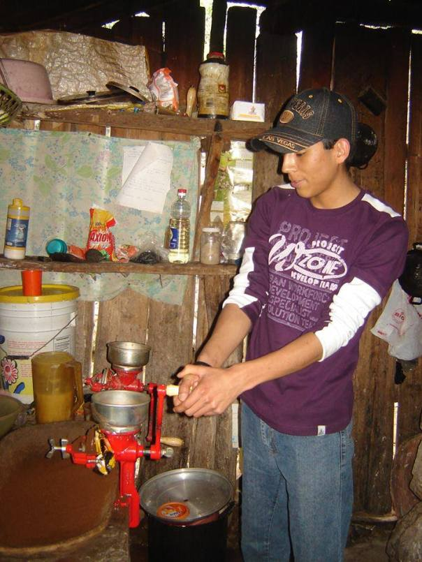 A Mission Volunteer tries out the coffee grinder