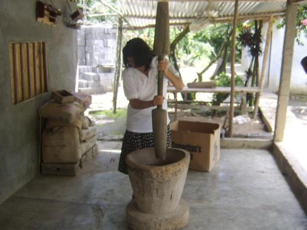 The first step in grinding the coffee beans.  The wooden mortar and pestle resembles the essential tool used in Africa and worldwide.